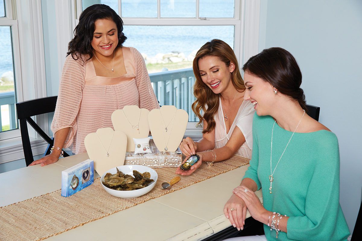 Woman showing two other women an opened oyster with a pearl inside.