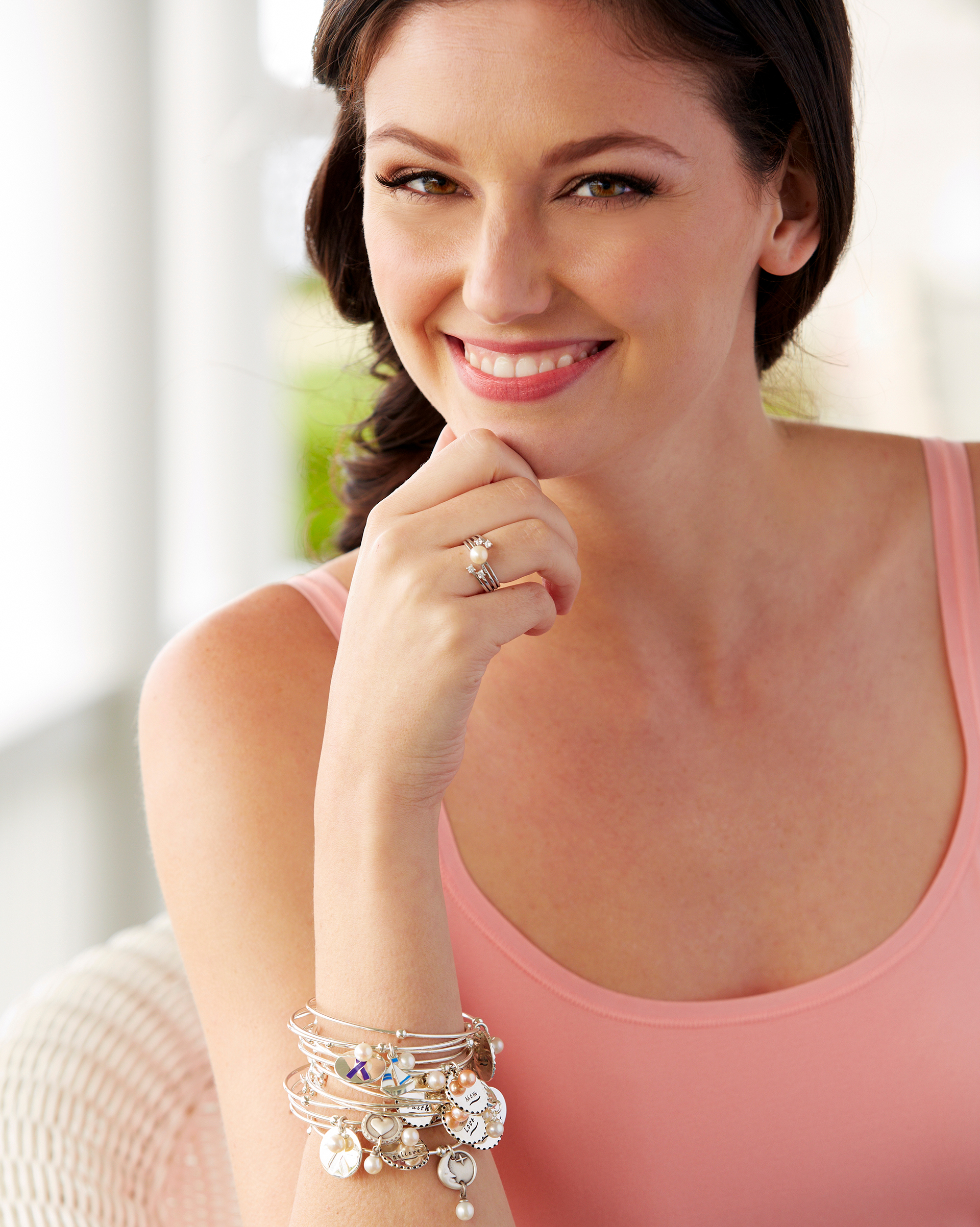 Woman posing wearing a pearl ring and bracelet.